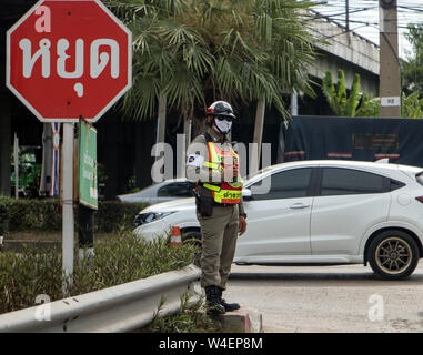 A traffic cop directing traffic on the road. Policeman control traffic at crossroads in city street. - Stock Photo