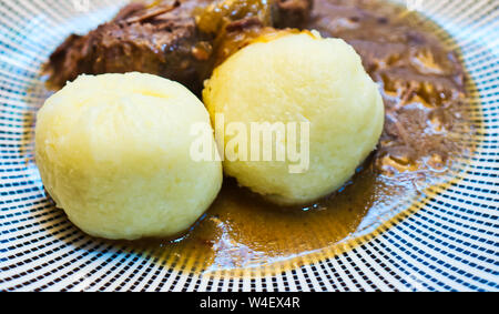Typical German dumplings, half raw and half boiled potatoes, on a sauerbraten with brown sauce - Stock Photo