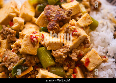 Mapo Doufu also known as Mapu Tofu, a spicy Asian dish made from minced meat and tofu cubes with spring onions and lots of chili, close up - Stock Photo