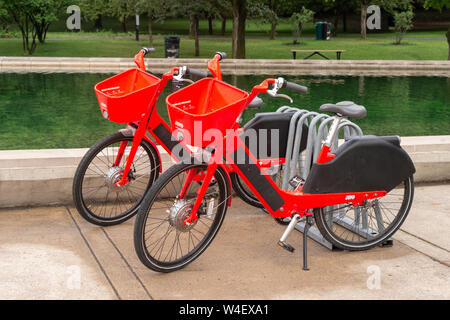 Montreal, Canada - 21 July 2019: Uber Jump electric bikes locked to city to a bike rack. - Stock Photo
