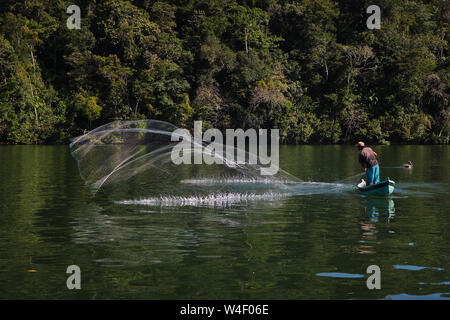 man fishing in a boat in a river with a net - Stock Photo