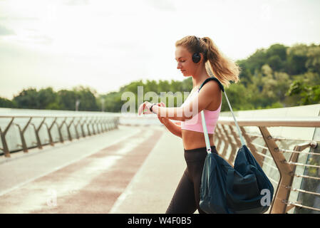 Workout results. Young sporty woman in headphones carrying bag and looking at her sport bracelet while standing on the bridge. Motivation. Healthy lifestyle. Sport concept - Stock Photo
