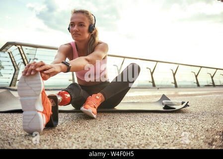 Morning exercises. Young beautiful woman in headphones with leg prosthesis listening music and stretching her leg while sitting on the bridge. Disabled sport concept. Motivation. Healthy lifestyle - Stock Photo