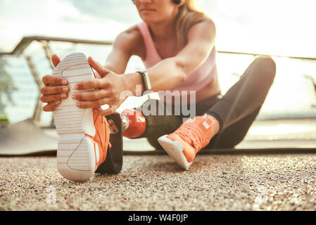 Stretching exercises. Cropped photo of young beautiful woman in headphones with leg prosthesis listening music and stretching her leg while sitting on the bridge. Disabled sport concept. Motivation. Healthy lifestyle - Stock Photo
