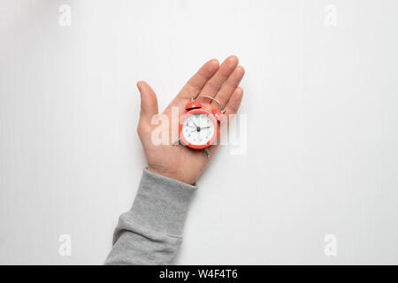The hand of a young man holds a red alarm clock. Time, sleep, awakening concept.