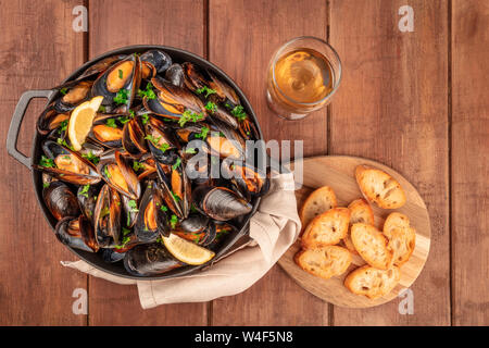 Marinara mussels, moules mariniere, with toasted bread and white wine, in a cooking pot, shot from above on a dark rustic wooden background - Stock Photo