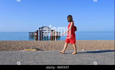 Brighton UK 23rd July 2019 - Visitors enjoy the early morning hot sunshine by the West Pier in Brighton . Heatwave conditions are forecast for the South East of Britain with temperatures expected to reach the mid thirties today and over the next few days . Credit: Simon Dack / Alamy Live News - Stock Photo
