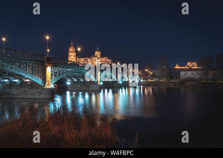 Salamanca Skyline view with Cathedral and Enrique Estevan Bridge from Tormes River at night - Salamanca, Castile and Leon, Spain - Stock Photo