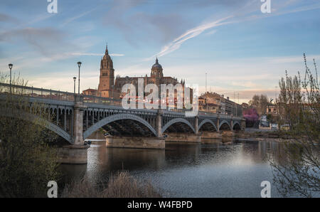 Salamanca Skyline view with Cathedral and Enrique Estevan Bridge from Tormes River at sunset - Salamanca, Castile and Leon, Spain - Stock Photo