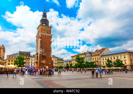 Krakow, Poland - June 18, 2019: People near Cloth Hall and Town Hall Tower in the main market square Rynek Glowny - Stock Photo