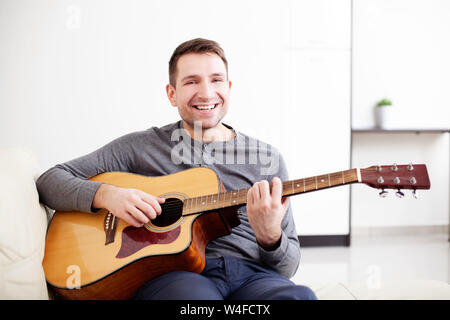 Handsome young man playing guitar, sitting on sofa