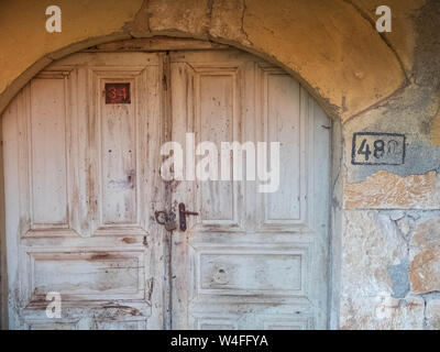 Wooden doors of the old abandoned stone mansion. - Stock Photo