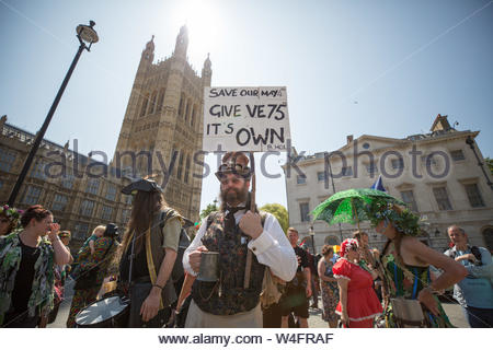 London, UK. 23rd July 2019. Morris dancers protest outside Parliament in Westminster over the Government's decision to move next year's May Day bank holiday from its traditional Monday to the following Friday. The move switches the holiday to May 8th in order to celebrate the 75th anniversary of VE Day. Morris Dancers claim the switch will disrupt hundreds of festivals and events nationwide, harming local economies. Morris Dancers are requesting an additional Bank Holiday instead. Credit: Guy Corbishley/Alamy Live News - Stock Photo