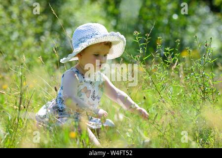 Gower, Wales, UK. 23rd July 2019. UK Weather: Pictured is toddler Lillian Joy, enjoying the scorching sunshine in a summer dress and hat, on the Gower Peninsular in South Wales, as temperatures soar across the UK at the start on the Summer school holidays, on the hottest day of the year to date. Credit : Robert Melen/Alamy Live News - Stock Photo