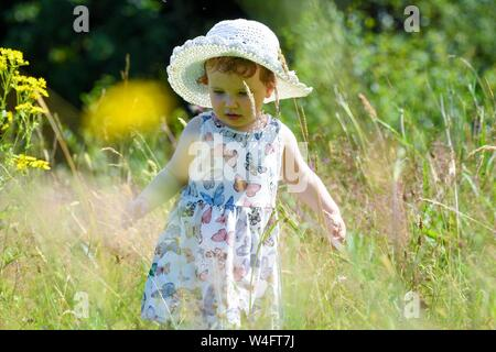 Gower, Wales UK. 23rd July 2019. UK Weather: Pictured is toddler Lillian Joy, enjoying the scorching sunshine in a summer dress and hat, on the Gower Peninsular in South Wales, as temperatures soar across the UK at the start on the Summer school holidays, on the hottest day of the year to date. Credit : Robert Melen/Alamy Live News - Stock Photo
