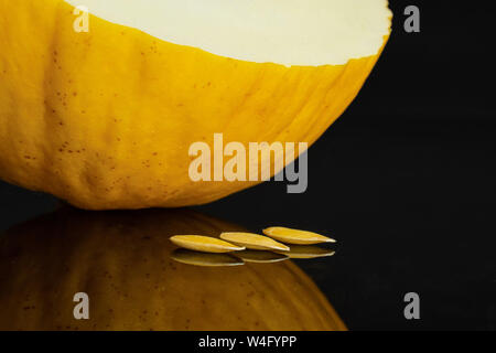 One half and three seeds of fresh yellow melon canary isolated on black glass - Stock Photo