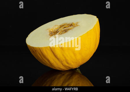 One half of fresh yellow melon canary isolated on black glass - Stock Photo