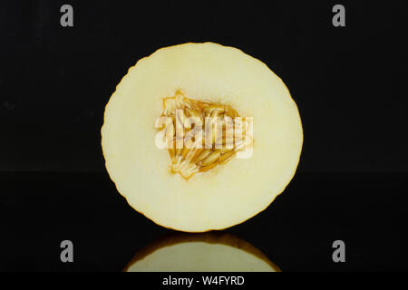 One half of fresh yellow melon canary cross section isolated on black glass - Stock Photo