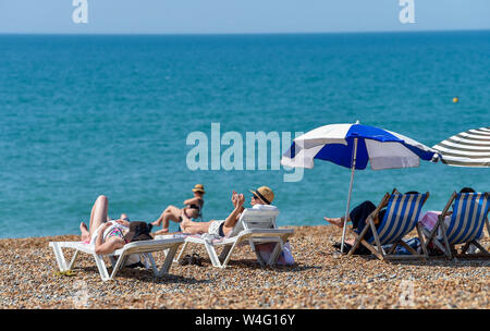 Brighton UK 23rd July 2019 - Sunseekers flock to Brighton Beach which is bathed in glorious hot sunshine today . Heatwave conditions are forecast for the South East of Britain with temperatures expected to reach the mid thirties today and over the next few days . Credit: Simon Dack / Alamy Live News - Stock Photo