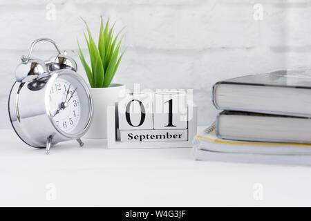 back to school,September 1 on the calendar,alarm clock and school supplies on the table - Stock Photo