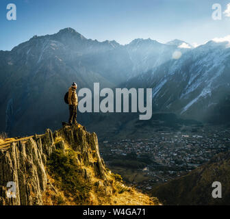 Young tourist in bright hat, black trousers with a backpack stands on cliff's edge and looking at the misty mountain village and glacier at sunrise - Stock Photo