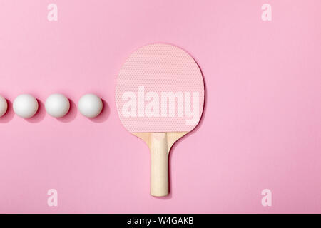 flat lay with table tennis balls and racket on pink background - Stock Photo
