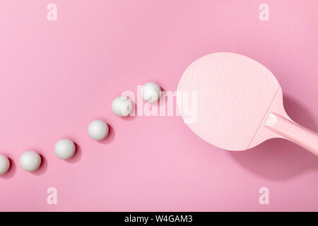 top view of white table tennis balls and racket on pink background - Stock Photo