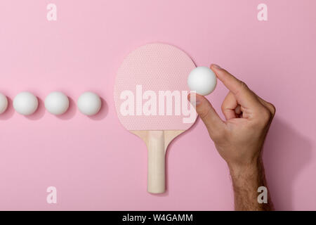 cropped view of man holding white table tennis ball near racket on pink background - Stock Photo