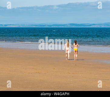 Gullane Bents, East Lothian, Scotland, United Kingdom, 23rd July 2019. UK Weather: start of a heatwave brings people to the sandy beach on the East Lothian coastline. Two girls in bikinis walk on the beach - Stock Photo
