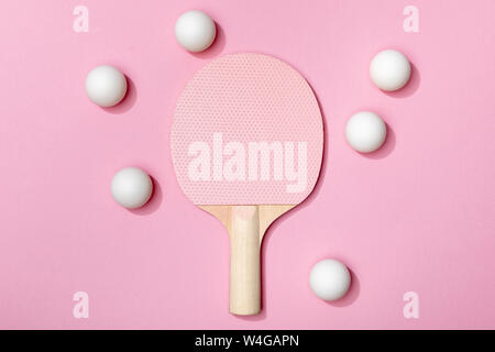 top view of white table tennis balls near wooden pink racket on pink background - Stock Photo