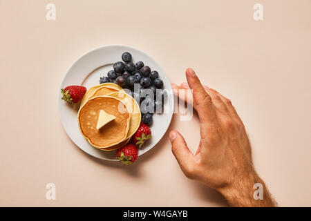 cropped view of man touching plate with pancakes and berries on pink - Stock Photo