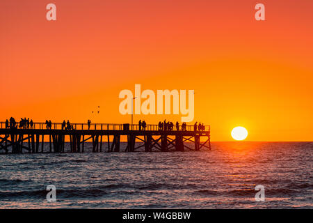 Semaphore Beach  jetty with people at sunset, South Australia - Stock Photo