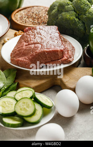 close up view of raw meat on wooden chopping board near eggs and cucumbers, , ketogenic diet menu - Stock Photo