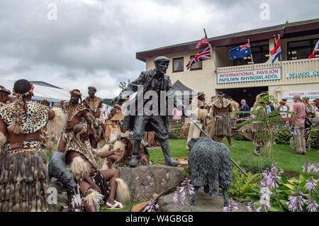 Zulu warriors beside the drover's statue at the Royal Welsh showground in Llanelwedd. Visit of King Goodwill of the Zulu Nation to the Royal Welsh Show (RWAS) at Builth Wells. Llanelwedd, Powys, Wales. - Stock Photo