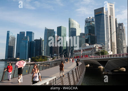 19.07.2019, Singapore, Republic of Singapore, Asia - Visitors at the riverfront in Marina Bay with the city skyline of the central business district.