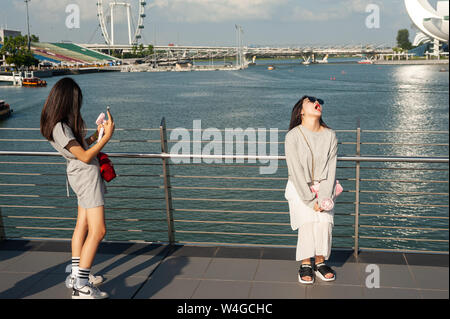 19.07.2019, Singapore, Republic of Singapore, Asia - Tourists pose for photos along the Singapore River in Marina Bay.