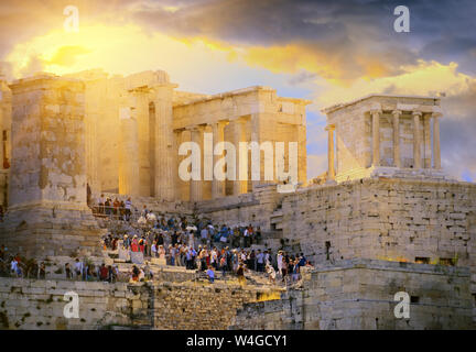 Dramatic sunrise over the antique Acropolis of Athens. Tourists wander about the Athenian Acropolis in the morning. Greece - Stock Photo