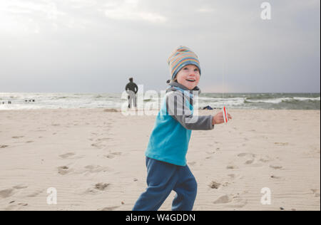 Happy little girl playing with kite on the beach