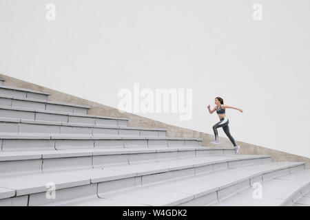 Young woman running on concrete bleachers - Stock Photo