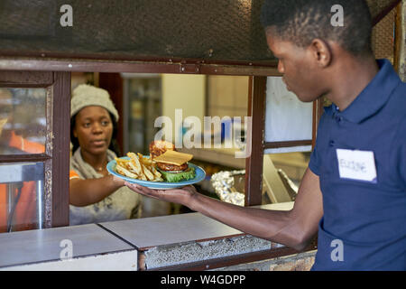 Young waiter taking delivered food from the restaurant kitchen, South Africa - Stock Photo