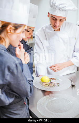 Junior chef showing his prepaired dessert on plate - Stock Photo