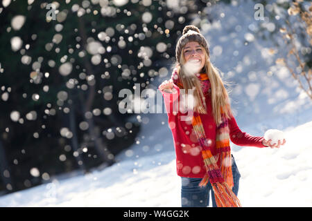 Young blond woman throwing with snow in winter - Stock Photo