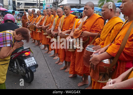 A market vendor in Phuket Town, Thailand,  bows to and greets Buddhist monks with a traditional 'wai', the monks on their ritual morning alms round - Stock Photo