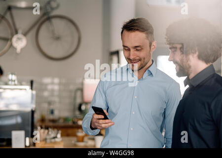 Business partners in a coffee shop having a meeting, using smartphone