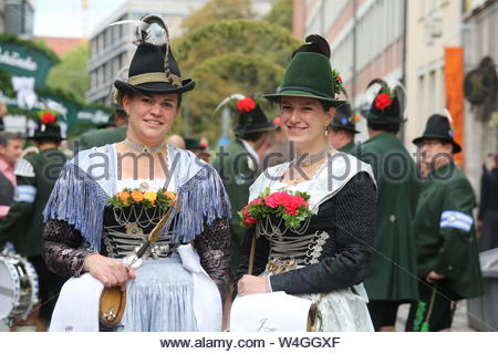 Two ladies in traditional tracht pose for the camera at the start of the Oktoberfest parade in Munich, Germany - Stock Photo