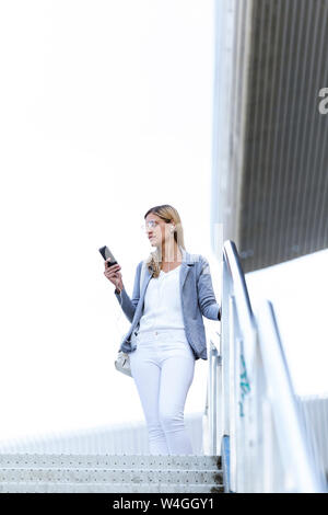 Young businesswoman listening to music with mobile phone on stairs - Stock Photo