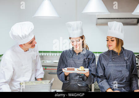 Junior chef showing her prepaired dessert on plate - Stock Photo