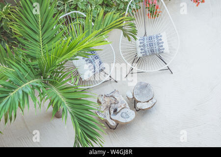 Outdoor chairs and wooden tables standing besides a palm tree on sandy beach - Stock Photo