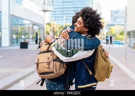 Two happy casual businessmen embracing in the city, Barcelona, Spain