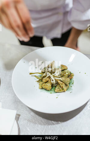 Junior chef prepairing a dessert on plate - Stock Photo